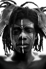 Portrait of young african man with dreadlocks and traditional face paint, hands pulling his hair, black and white