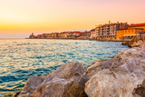 Beautiful sunset above the Piran city, Slovenia. Magic sun light above the Adriatic sea and Piran coast. Soft light of sky and blue water in foreground. Stone wall near Piran harbor - 243168196