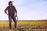 Cowboy standing in a field at sunset - 243173182