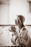 Young woman with cup of coffee sitting at table in near fairy lights in evening time. . Image in sepia color style