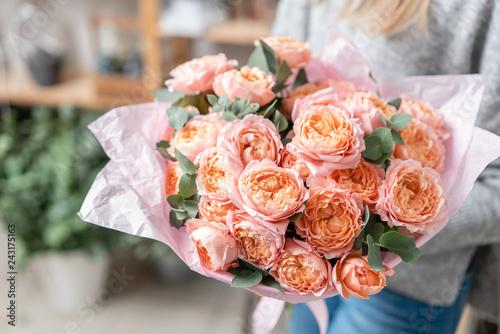 Leinwandbild Motiv beautiful fresh cut bouquet of mixed flowers in woman hand. the work of the florist at a flower shop
