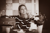 Young lady in sweater sitting at the table in breakfast time with cup of coffee and cake at the kitchen. . Image in sepia color style - 243176919