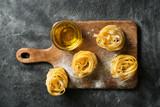 Tagliatelle pasta uncooked, making spaghetti background, black texture