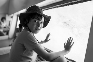 The boy is watching the underwater world through the large porthole below of the waterline a tourist ship. Black and white.