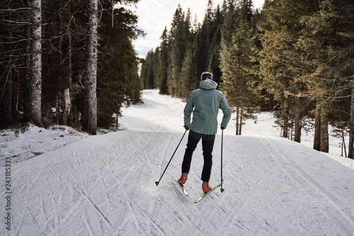 Caucasian man enjoying his free time cross country skiing in the woods, covered with snow