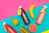 Bottles of juice and fruits on a colored background