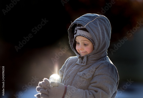 Foto Murales Boy with magical light ball on snow