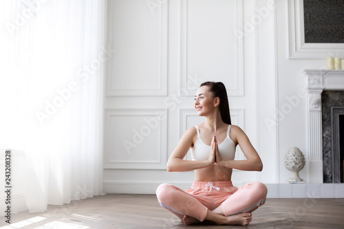 Wall mural Portrait of young happy girl practicing yoga.
