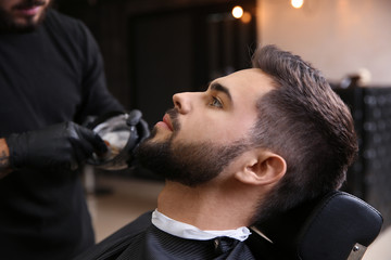 Young man visiting barbershop. Professional shaving service