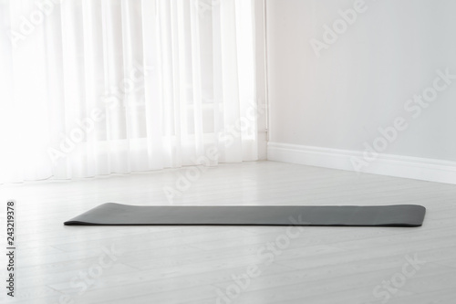 Leinwanddruck Bild Rubber yoga mat on floor indoors. Space for text