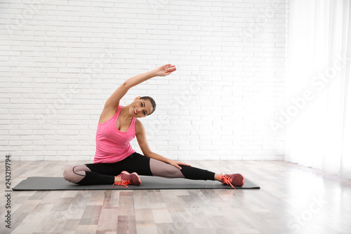 Leinwanddruck Bild Young beautiful woman practicing yoga at home, space for text. Workout and fitness