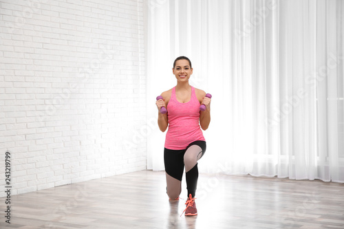 Leinwanddruck Bild Young beautiful woman with dumbbells doing exercise at home. Workout and fitness