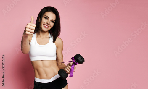 Leinwanddruck Bild Girl working out with big weight dumbbell smiling  and show thumb up on pink