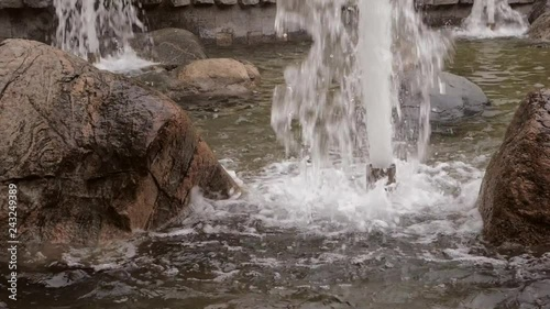 Big brown wet stones and streams of water spurting from pipes in fountain