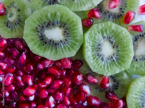 pomegranate fruit seeds and sliced kiwi fruit closeup