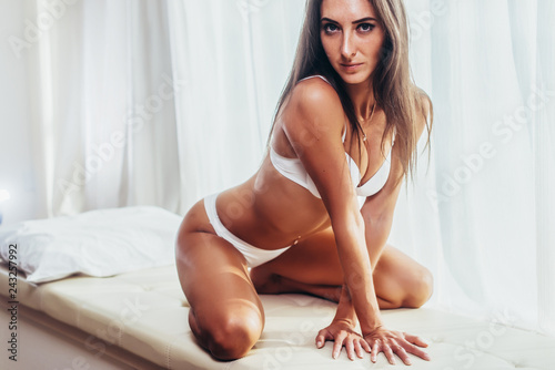 Sexy tanned young brunette female model in underwear sitting posing in white interior with curtains in the background. - 243257992