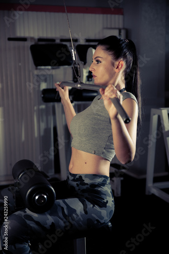 Beautiful young caucasian woman with black hair workout in fitness gym