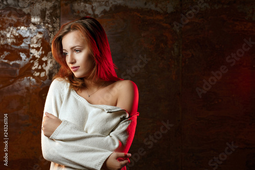 Adorable young model wearing sweater with naked shoulders, posing with red light. Empty space - 243261104