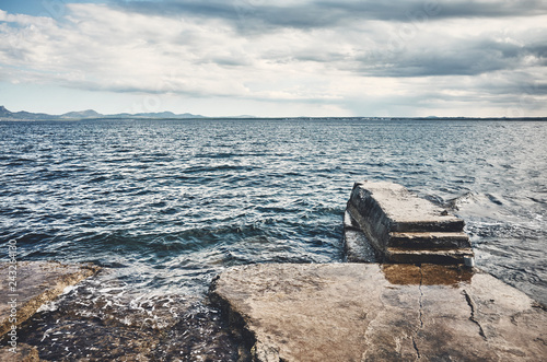 Seascape with a concrete pier, color toned picture.