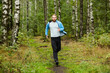 Young active man running down forest path surrounded by green grass and trees on summer weekend