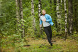Young sportsman in activewear having jog training in the forest on summer morning