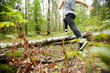 Back view of young sportsman running over log on the forest path while training in the morning