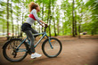 Young sportswoman riding bicycle along road in the forest with blurry trees on both sides
