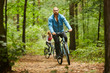 Active guy in sportswear cycling along forest path on summer day with his girlfriend moving after him