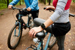 Young sportswoman with smartwatch and bicycle and her boyfriend having short break during cycle chill