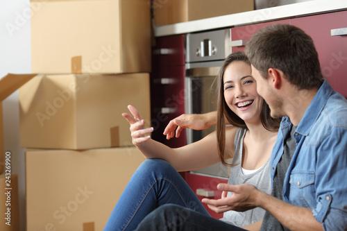 Leinwandbild Motiv Smiley couple moving home talking on the floor