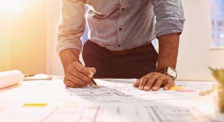 Architect hands working on blueprint © Rido