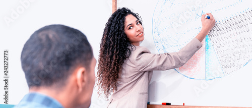Poster Young businesswoman showing her colleague the business trend