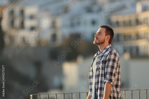 Leinwanddruck Bild Relaxed man in a town breathing fresh air