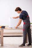 Young handsome contractor repairing fridge