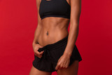 Cropped photo of african american woman in black sportswear standing, isolated over red background - 243275963