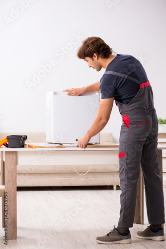 Young handsome contractor repairing fridge © Elnur