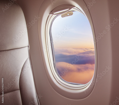 Airplane interior with window view of sunset above clouds. - 243279994