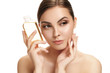 Leinwanddruck Bild - Beauty concept. The caucasian pretty woman with perfect skin holding oil bottle at studio