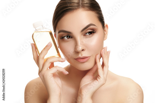 Leinwanddruck Bild Beauty concept. The caucasian pretty woman with perfect skin holding oil bottle at studio