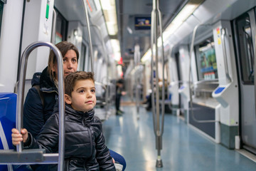 Mother and son travelling on the subway