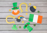 holidays and celebration concept - st patricks day decorations or party props made of paper on grey wooden boards background - 243284336