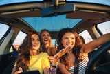Three female friends enjoying traveling at vacation in the car. - 243284722