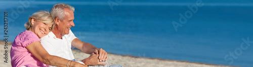 Leinwandbild Motiv Happy Romantic Senior Couple Sitting Together on Beach