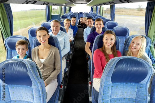 transport, tourism and travel concept - group of happy passengers travelling by bus - 243287992