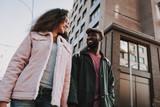 Smiling beloved couple walking on city background - 243288179
