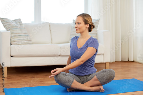 Wall mural mindfulness, spirituality and healthy lifestyle concept - woman doing twist in lotus pose at home