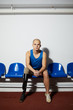 Disable young sportsman with handicap sitting on blue plastic chair along wall before competition
