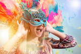 Beautiful young woman in carnival mask. Beauty model woman wearing masquerade mask at party over holiday background with magic glow. Christmas and New Year celebration. Glamour lady with perfect make - 243293106