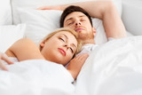 people, rest and relationships concept - happy couple sleeping in bed at home