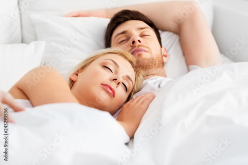 people, rest and relationships concept - happy couple sleeping in bed at home © Syda Productions